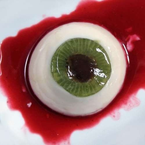 Halloween eye made with kiwi, cream, and red sweet sauce